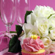 Stock Photo: Wedding bridal bouquet of white roses on pink background with pink cupcake and pair of two champagne flute glasses. Vertical.