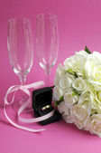 Wedding bridal bouquet of white roses on pink background with pair of champagne flute glasses and gold wedding ring in black jewelry box. Vertical. — Stockfoto