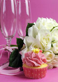 Wedding bridal bouquet of white roses on pink background with pink cupcake and pair of two champagne flute glasses. Vertical. — Stock Photo