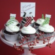 Christmas decorated chocolate red velvet cupcakes with white frosting and red and green festive decorations on pink cake stand — Stok fotoğraf