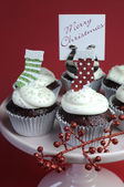 Christmas decorated chocolate red velvet cupcakes with white frosting and red and green festive decorations on pink cake stand — Stock Photo