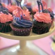 Female high heel shoes decorated pink and purple red velvet cupcakes with high heel shoes for teenage, female birthday, or wedding bridal shower, on party table setting. — Foto de Stock