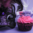 Pink and purple masquerade masks decorated party cupcake with pink frosting — Stock Photo #26907423