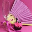 Pink party cupcake with black stilleto high heel shoe with champagne glass, fan and chocolates — Stock Photo
