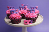 Pink and purple masquerade masks decorated party cupcakes with pink frosting for teenage, birthday, New Years Eve, or wedding bridal shower party — Foto Stock