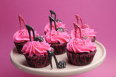 Female high heel shoes decorated pink and black red velvet cupcakes — Stock Photo