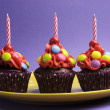 Three bright candy covered cupcakes with birthday candles on yellow polka dot plate against a purple background — Stock Photo