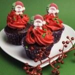 três bolinhos de Natal em invólucro de bolinhas roxas com decoração vermelha de geada e santa contra um fundo verde festiva — Foto Stock #26963737