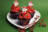 Three Christmas Cupcakes in purple polka dot wrapper with red frosting and santa decoration against a festive green background — Foto de Stock