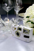 Close up of detail on wedding breakfast dining table setting with wedding camera — Stock Photo