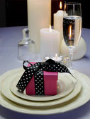 White Satin Wedding Table Setting Detail with pink wedding favor gift — Stock Photo