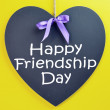 Celebrate International Friendship Day on August 4, with Happy greeting on heart shape blackboard — Stock Photo #27531357
