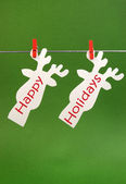 Celebrate seasonal and Christmas holidays with a bright and vivid pegs on a line message greeting, Happy Holidays across funny cute reindeer faces against a holly green festive background. — Stock Photo