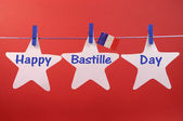Happy Bastille Day greeting written across white stars with a French flag hangning from blue pegs on a line — Stock Photo