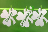 Celebrate St Patricks Day holiday on March 17 with Happy St Patricks Day message greeting written across white shamrocks hanging from pegs on a line — Stock Photo