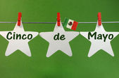 Cinco de Mayo message greeting written across white stars and Mexico flag hanging pegs on a line — Stock Photo