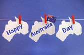 Happy Australia Day message greeting written across white Australian maps and flag hanging pegs on a line — Stock Photo