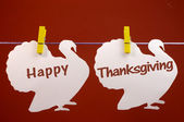 Happy Thanksgiving message greeting written across white turkeys hanging from pegs on a line — Stock Photo