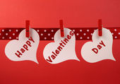 Happy Valentines Day message greeting written across white heart tags hanging from red pegs on a line — Stock Photo