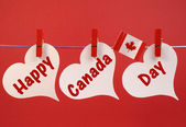 Happy Canada Day message greeting with the Canadian maple leaf flag hanging from pegs on a line — Stock Photo