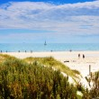Sunny day at the beach with sailing boat in background. Taken at Henley Beach, South Australia. — Foto Stock