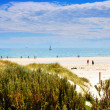 Sunny day at the beach with sailing boat in background. Taken at Henley Beach, South Australia. — Stock Photo