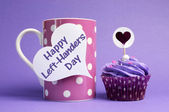 Happy Left Handers Day message written on white heart shape tag on pink polka dot mug with purple cupcake — Stock Photo