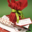 Traditional red & green Christmas lunch or dinner table setting with gift wrapped plum pudding. — Stok fotoğraf