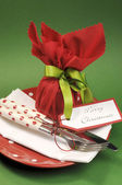 Traditional red & green Christmas lunch or dinner table setting with gift wrapped plum pudding. — Stock Photo
