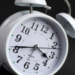 Classic white alarm ticking clock on black background — Stock Photo