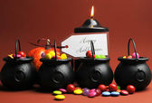 Halloween trick or treat candy in cauldrons — Stock Photo