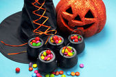 Halloween witch hat and cauldrons full of candy — Stock Photo