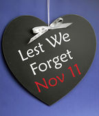 Lest We Forget message written on heart shape blackboard — Stock Photo