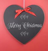 Merry Christmas greeting message on heart shape blackboard — Stock Photo
