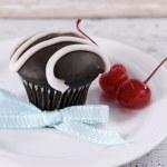 Chocolate cupcake on shabby chic table with maraschino cherries — Stock Photo #35736457