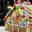 Fun children Christmas gingerbread house in front of Christmas tree — Stock Photo