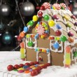 Fun children Christmas gingerbread house in front of Christmas tree — Stock Photo #35868719