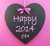 Happy New Year 2014 message greeting written on heart shape blackboard — Stock Photo