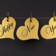 Happy New Year message greeting text on gold hearts hanging from pegs on a line — Stock Photo
