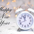 Happy New Year message with white retro clock showing five to midnight — Stock Photo