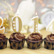Happy New Year chocolate cupcakes with 2014 candles against bokeh Christmas lights — Stock Photo #37468739