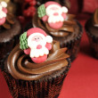 Merry Christmas chocolate cupcakes with Santa faces against red festive background. — Stock Photo #37468789