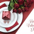 Happy Valentines Day dining table setting, with red hearts, gift, and red roses, with greeting. — Stock Photo