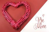 Pink red rattan cane love heart on red and white background with Be Mine message greeting. — Foto Stock