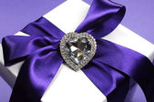 Beautiful purple ribbon on white gift for special occasions. — Stock Photo