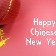 Happy Chinese New Year text greeting with traditional decorations on red background. — Stock Photo
