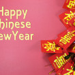 Happy Chinese New Year text greeting with traditional decorations on red background. — Stock Photo #39718687
