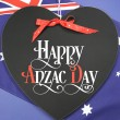 Stock Photo: Happy Anzac Day, April 25, national public holiday celebration for returned soldiers, greeting on heart shaped blackboard