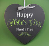 Happy Arbor Day, Plant a Tree, greeting message sign on heart shaped blackboard against a green background. — Stock Photo