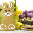 Happy Easter yellow and lime green theme gingerbread bunny cookie with basket, tulips, and candy birds eggs in nest — Stock Photo